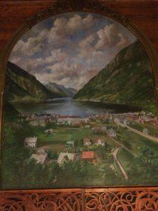 Biletet visar maleriet som heng over scena i Odda ungdomshall. Maleriet er av Odda i gamle dagar med fjorden i bakgrunnen.